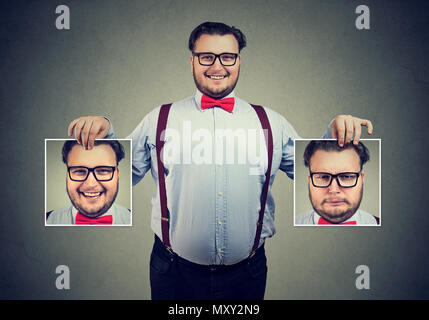Young cheerful man in glasses holding pictures with good and bad emotions having mood swings and smiling at camera - Stock Photo