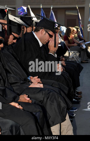 161214-N-AV746-231 CORONADO, Calif. (Dec. 14, 2016) Sailors, assigned to Naval Special Warfare, pray during a graduation ceremony at Naval Base Coronado. Twenty-eight Navy SEALs and Special Warfare Combatant Craft Crewmen received bachelor's degrees in organizational leadership and one operator earned his master's degree in strategic leadership from the University of Charleston. (U.S. Navy photo by Petty Officer 2nd Class Timothy M. Black/Released) - Stock Photo