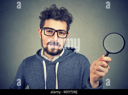 Bearded scrupulous man in glasses holding magnifying glass looking at camera on gray background. - Stock Photo