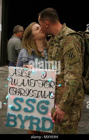 A Soldier of 6th Squadron, 8th Cavalry Regiment, 2nd Infantry Brigade Combat Team, 3rd Infantry Division reunites with a loved one at Fort Stewart, Georgia, December 13, 2016. Troopers of 6-8 Cav. returned from a five-month rotation supporting Joint Multinational Training Group-Ukraine, building sustainable training capacity and capability within Ukrainian land forces. (U.S. Army photo by Staff Sgt. Candace Mundt/Released) - Stock Photo