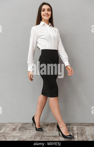 Full length portrait of adorable young woman 20s with long brown hair in white shirt and black skirt posing at camera with smile isolated over white b - Stock Photo