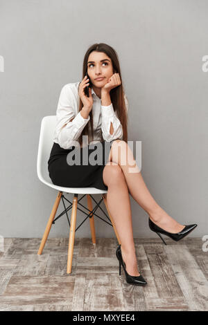Full length portrait of adorable woman with long brown hair in business wear sitting on chair with boring look and having mobile conversation isolated - Stock Photo