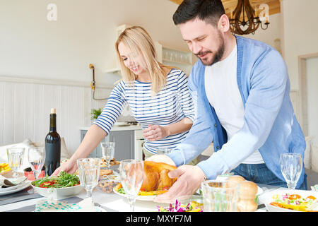 Portrait of modern young couple setting dinner table  while waiting for guests  in sunlit dining room at home, focus on mature bearded in foreground - Stock Photo