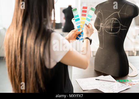 Back view portrait of focused Asian woman working in fashion design choosing color palette holding swatches standing at table by sewing dummy in moder - Stock Photo