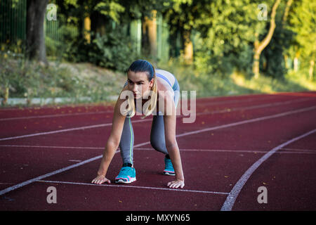 sports beautiful girl on the treadmill ready to run a big stadium, closeup - Stock Photo