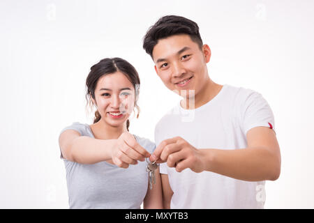 Couple with keys to new home. Happy smiling young couple showing a keys of their new house. - Stock Photo
