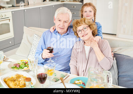 Portrait of modern senior man and woman posing with little granddaughter sitting at dinner table and smiling happily looking at camera , copy space - Stock Photo