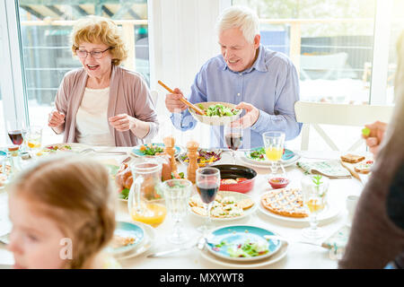 Portrait of happy family enjoying dinner together sitting round festive table with delicious dishes, focus two grandparents, copy space - Stock Photo