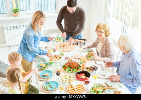 High angle portrait of big happy family enjoying dinner together sitting round festive table with delicious dishes,  young woman serving food during   - Stock Photo