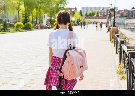 Teenage student girl walking down the street with backpack. Back to school, back view - Stock Photo