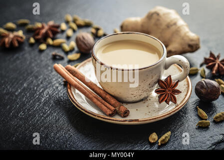 Traditional indian drink - masala tea with spices on black stone  background - Stock Photo