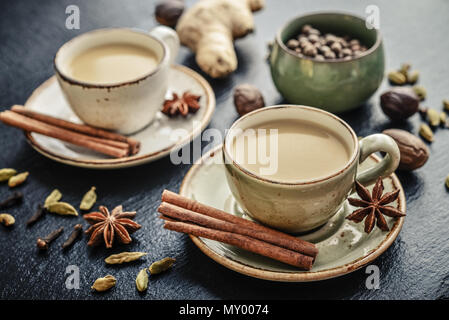 Traditional indian drink - masala chai tea (milk tea) with spices on black slate  background - Stock Photo