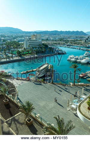 Lagoon and marina in Eilat in southern Israel. The city and hills of Aqaba, Jordan are in the background. - Stock Photo