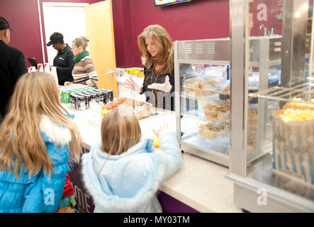 Theresa McDonald (first from right), an Army and Air Force Exchange Service loss prevention manager, serves customers at the movie theater's concession stand at Joint Base Andrews, Md., Dec. 16, 2016. The newly-renovated theater resumed showing movies after stopping more than five years ago. (U.S. Air Force photo by Staff Sgt. Joe Yanik) - Stock Photo