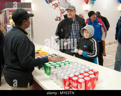 Master Sgt. Robert Bedwell (third from left), Air National Guard Bureau Command Post training and standardization manager, and his son, Connor, place an order with Shavown Brown, movie theater attendant, at the movie theater concession stand at Joint Base Andrews, Md., Dec. 16, 2016. The theater will close again late January 2017 so new seats can be installed before the grand opening the following month. (U.S. Air Force photo by Staff Sgt. Joe Yanik) - Stock Photo