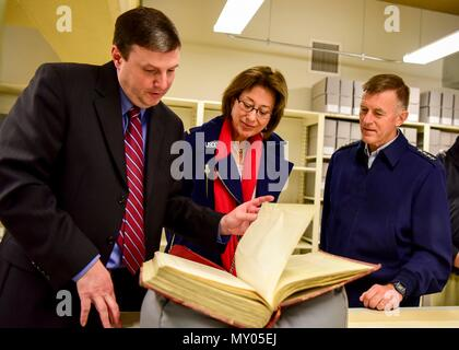 A National Archives member shows U.S. Coast Guard Commandant Adm. Paul Zukunft and his wife Fran DeNinno-Zukunft the original print of the Coast Guard Act of 1915, at the National Archives in Washington, D.C., Dec. 30, 2016. Passed by Congress and signed into law by President Woodrow Wilson, the Coast Guard Act of 1915 combined the Life-Saving Service and the Revenue Cutter Service into what is known today as the U.S. Coast Guard. (U.S. Coast Guard photo by Petty Officer 2nd Class Diana Honings/released) - Stock Photo