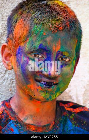 Young boy celebrating of Holi festival with colored powder on face, Yerawada - Stock Photo