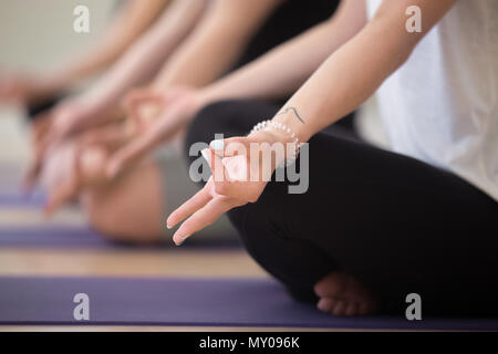 Young sporty woman practicing yoga, sitting in in Lotus pose, with mudra gesture, working out, indoor close up, yoga studio. Mindfulness, wellness, we - Stock Photo