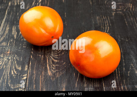 Two fresh persimmon fruit on wooden background - Stock Photo