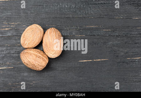Three dry nutmeg on an empty wooden background - Stock Photo