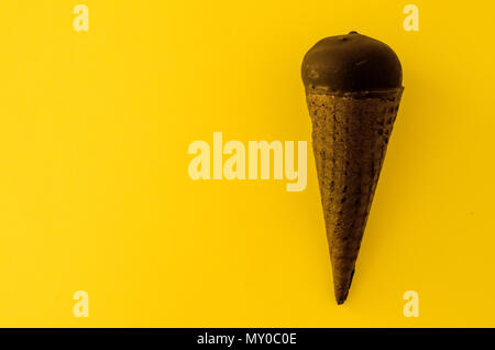 Vanilla ice cream with cranberry jam in a sugar cone dipped in chocolate on yellow background.Pastel colour.Cool off in the hot summer.Copy space left - Stock Photo