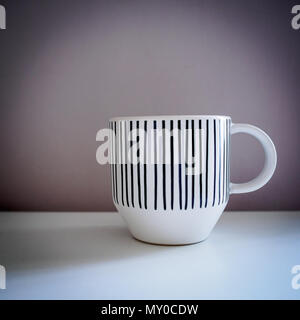 White mug with black lines decorations on a white table. Vintage look filter. Square format. - Stock Photo