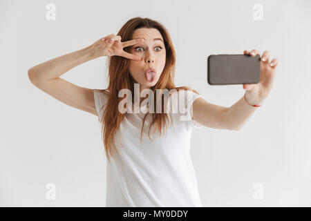 Funny woman in casual clothes making selfie on smartphone while showing her tongue and peace gesture over grey background - Stock Photo