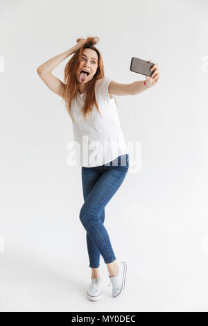 Full length image of Funny woman in casual clothes making selfie on smartphone while holding her hair and showing her tongue over grey background - Stock Photo