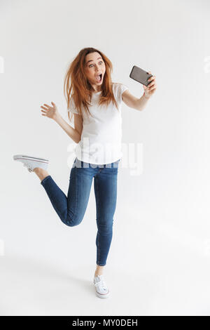 Full length image of Screaming woman in casual clothes making selfie on smartphone and jumping over grey background - Stock Photo