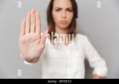 Portrait of a serious young business woman showing stop gesture with her palm isolated over white background - Stock Photo