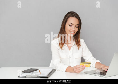 Portrait of a confident young business woman holding golden credit card while sitting at the office table and working on laptop computer isolated over - Stock Photo