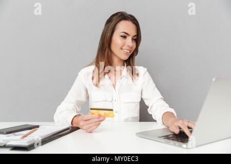 Portrait of a happy young business woman holding golden credit card while sitting at the office table and working on laptop computer isolated over whi - Stock Photo
