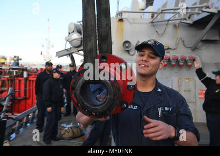 161219-N-JI086-022 - VALENCIA, Spain (Dec. 20, 2016) Petty Officer 3rd Class Enrique Gonzalez, from San Bernardino, Calif., hoists a fuel line adapter aboard the guided-missile destroyer USS Porter (DDG 78) as the ship prepares to take on fuel pier-side in Valencia, Spain, Dec. 20, 2016. Porter, forward-deployed to Rota, Spain, is conducting naval operations in the U.S. 6th Fleet area of operations in support of U.S. national security interests in Europe. (U.S. Navy photo by Seaman Ford Williams/Released) - Stock Photo
