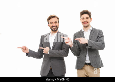 Portrait of a two satisfied business men pointing away isolated over white background - Stock Photo