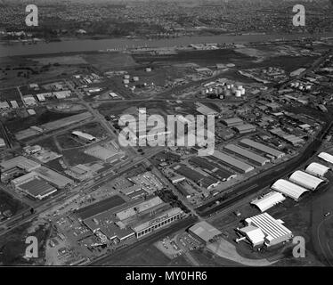 Ford Motor Factory, Eagle Farm, Brisbane, 1967. The Ford Motor Company of Australia, a subsidiary company of Ford Canada, established a motor vehicle assembly plant at Eagle Farm in 1926. The site had ready access to road, railway, and shipping facilities on the river. The factory played an important manufacturing role during WWII constructing a range of products and parts for the military forces of both Australia and the United States. The factory closed in 1998.  In the bottom right is the old Eagle Farm airport and in the background is Hamilton wharf on the Brisbane River. - Stock Photo