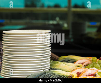 set white plates on the table, fruits in the background - Stock Photo