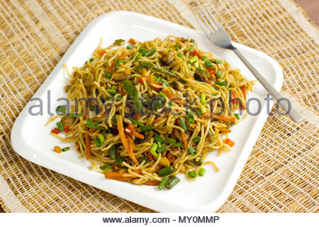 Veg Hakka noodles is an Indo Chinese stir fried noodles with vegetables and Chinese sauce. - Stock Photo