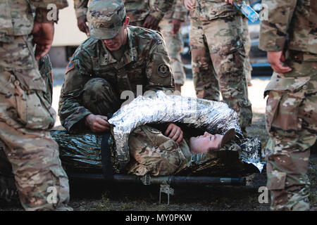 Pfc. Grant Granath (left) and Pfc. Jakob Willams (right), infantrymen assigned to1st Squadron, 2nd Cavalry Regiment, practice preparing a casualty for evacuation during combat lifesaver training withBattle Group Poland at Bemowo Piskie Training Area, Poland,May 30, 2018. Battle Group Poland is a unique, multinational coalition of U.S., U.K., Croatian and Romanian Soldiers who serve with the Polish 15th Mechanized Brigade as a deterrence force in support of NATO's Enhanced Forward Presence. (U.S. Army photo by Spc. Hubert D. Delany III) - Stock Photo