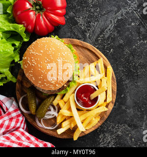 Hamburger, french fries, pickles and ketchup on wooden board. Fast food. Homemade burger and potato fries. Top view with copy space for text - Stock Photo