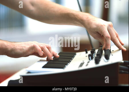A synthesizer player during a concert moves knobs and controls the sound. - Stock Photo