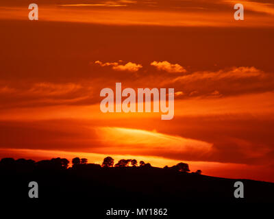 Ashbourne, Derbyshire. 5th Jun, 2018. UK Weather: spectacular sunset over the ancient woods Hazleton Clump Cairn near Thorpe taken from Ashbourne Derbyshire, Peak District National Park Credit: Doug Blane/Alamy Live News - Stock Photo
