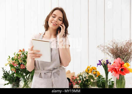 Young florist woman standing near table with different flowers in studio and calling to clients with notes in hand - Stock Photo