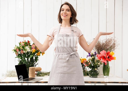 Smiling florist woman standing near table with different flowers in workshop and looking at camera with hands aside - Stock Photo