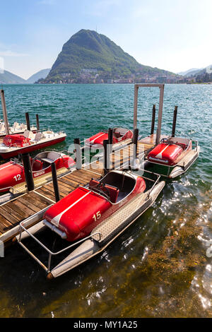 View of Lugano lakefront with the typical pedalos on a spring day, Canton Ticino, Switzerland. - Stock Photo