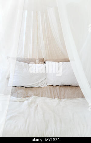 Four-poster bed with two pillows. Scandinavian simplicity design. Eco loft apartments - Stock Photo