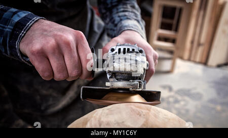 Close up of a young man carpenter in a suit, goggles   saws a man's head with a tree , using an angle grinder  in the workshop, around a lot of tools  - Stock Photo