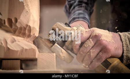 Experienced carpenter in work clothes    saws a man's head with a tree , using an angle grinder  in the workshop, carpenter's hands in sawdust - Stock Photo