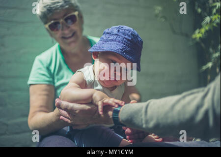 A little baby is playing with his grandparents in the backyard on a summer day - Stock Photo