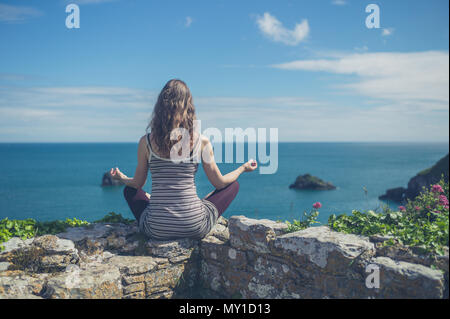 A young woman is sitting on a wall by the sea and is meditating - Stock Photo