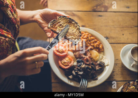 Young woman spreading butter on toast as part of a traditional english breakfast - Stock Photo